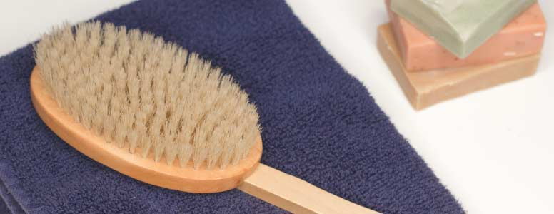 A dry body brush on a blue towel next to bars of soap