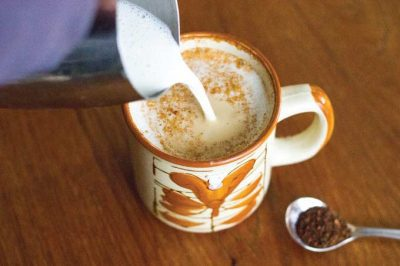 Pouring steamed milk into a mug with root coffee