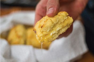 Holding a gluten-free biscuit with dripping honey