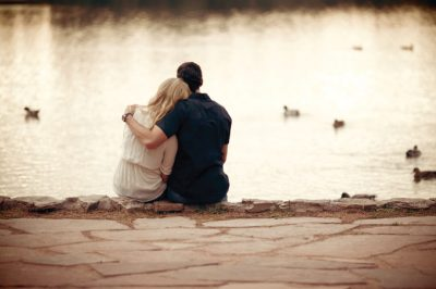 A man and woman hugging by a lake