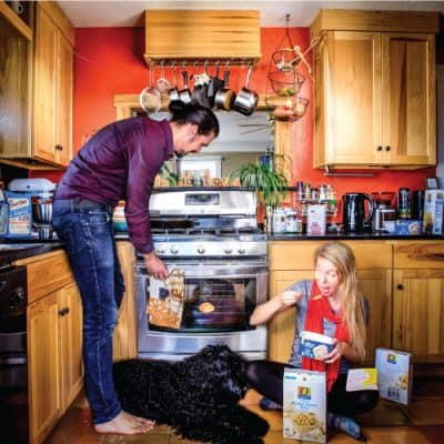 Pregnancy announcement picture husband wife and dog in kitchen with bun in oven